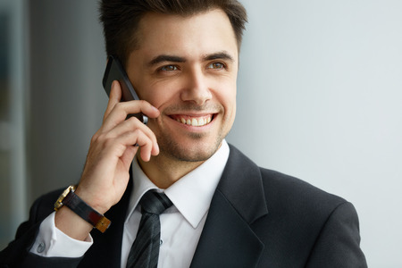 using phone: Businessman Talking on the Phone and Smiling