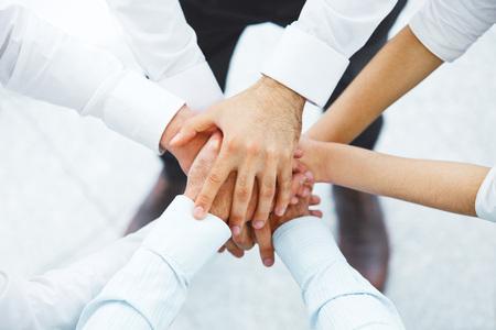 negocios internacionales: Equipo internacional de negocios que muestra la unidad con sus manos juntas