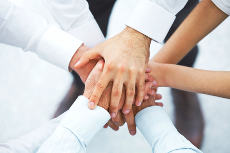 International business team showing unity with their hands together
