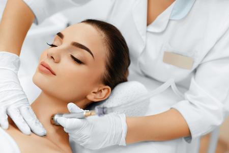 顔のスキンケア。ダイヤモンド マイクロダーマブレーション剥離の治療スパのサロンで美しい女性のクローズ アップ。クレンジング プロシージャ