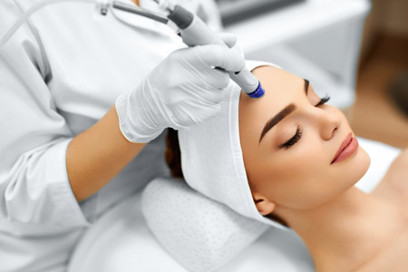 face: Face Skin Care. Close-up Of Woman Getting Facial Hydro Microdermabrasion Peeling Treatment At Cosmetic Beauty Spa Clinic. Hydra Vacuum Cleaner. Exfoliation, Rejuvenation And Hydratation. Cosmetology. Stock Photo