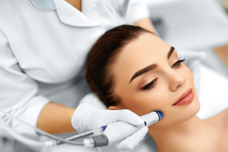 beauty treatment clinic: Face Skin Care. Close-up Of Woman Getting Facial Hydro Microdermabrasion Peeling Treatment At Cosmetic Beauty Spa Clinic. Hydra Vacuum Cleaner. Exfoliation, Rejuvenation And Hydratation. Cosmetology. Stock Photo
