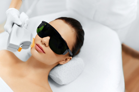 the photo: Skin Care. Young Woman Receiving Facial Beauty Treatment, Removing Pigmentation At Cosmetic Clinic. Intense Pulsed Light Therapy. IPL. Rejuvenation, Photo Facial Therapy. Anti-aging Procedures. Stock Photo