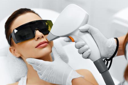 Cura del viso. Viso Depilazione laser. Estetista dà fronte Laser Epilazione Trattamento alla giovane donna di At Beauty Clinic. Cura del corpo. Hairless liscia e morbida pelle. Salute e Bellezza Concept. Archivio Fotografico