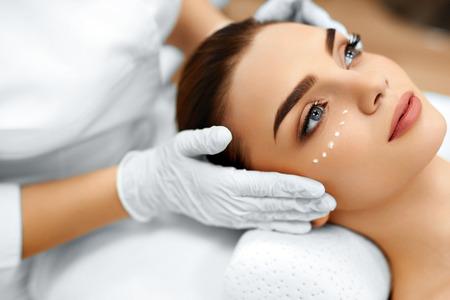 tratamientos corporales: Protección de la piel. Primer De Cosmetician que aplica el cosmético hidratante crema en la cara de la mujer joven. Cara de belleza. Tratamiento de spa En Salón de Belleza. Tratamiento de belleza facial.