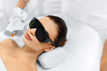 beauty treatment clinic: Skin Care. Young Woman Receiving Facial Beauty Treatment, Removing Pigmentation At Cosmetic Clinic. Intense Pulsed Light Therapy. IPL. Rejuvenation, Photo Facial Therapy. Anti-aging Procedures. Stock Photo