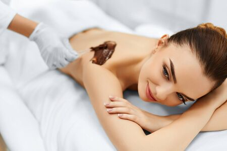 chocolate mask: Body Care. Spa Treatment. Portrait Of Beautiful Smiling Young Woman Receiving Cosmetic Chocolate Body Mask At Beauty Salon. Skin Care. Healthy Lifestyle