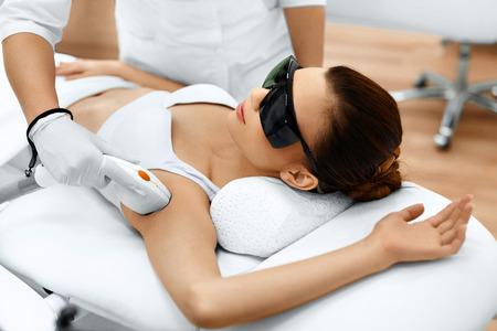 Körperpflege. Unterarm Laser-Haarentfernung. Kosmetikerin Entfernen Haare der jungen Frau, die Achselhöhle. Haarentfernung mit Laser-Behandlung in kosmetischen Schönheitsklinik. Hairless glatte und weiche Haut. Gesundheit und Beauty-Konzept. Standard-Bild