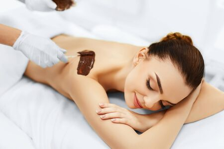 body mask: Body Care. Spa Treatment. Portrait Of Beautiful Smiling Young Woman Receiving Cosmetic Chocolate Body Mask At Beauty Salon. Skin Care. Healthy Lifestyle