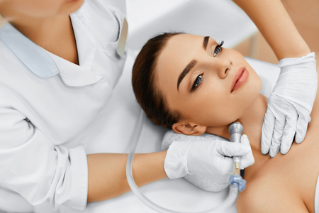 spa treatment: Face Skin Care. Closeup Of Beautiful Woman Getting Diamond Microdermabrasion Peeling Treatment In A Beauty Spa Salon. Cleansing Procedure. Cosmetology.