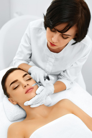 cosmetologies: Beauty Face. Plastic Surgery. Doctor Making Cosmetic Anti-aging Injection With Syringe Into Womans Face In Beauty Salon. Reduction Of Wrinkles Treatment. Cosmetology. Mesotherapy