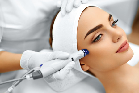 girl care: Face Skin Care. Close-up Of Woman Getting Facial Hydro Microdermabrasion Peeling Treatment At Cosmetic Beauty Spa Clinic. Hydra Vacuum Cleaner. Exfoliation, Rejuvenation And Hydratation. Cosmetology. Stock Photo
