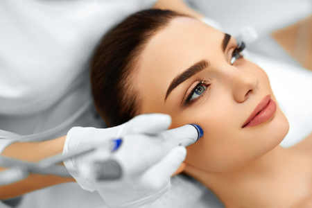 clinics: Face Skin Care. Close-up Of Woman Getting Facial Hydro Microdermabrasion Peeling Treatment At Cosmetic Beauty Spa Clinic. Hydra Vacuum Cleaner. Exfoliation, Rejuvenation And Hydratation. Cosmetology. Stock Photo