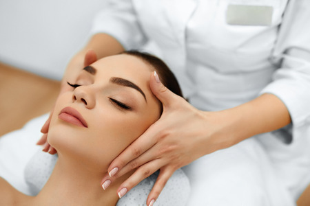 volti: Pelle e cura del corpo. Primo Piano Di Un Giovane donna ottenendo trattamento spa al salone di bellezza. Spa Massaggio Viso. Trattamento di bellezza viso. Spa Salon.