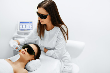 Hautpflege. Junge Frau empfangen Gesichtsbehandlung, Entfernen Pigmentierung Bei Cosmetic Clinic. Intense Pulsed Light Therapy. IPL. Verjüngung, Foto Facial Therapy. Anti-Aging-Verfahren.