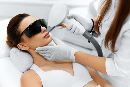페이스 케어. 얼굴 레이저 제모. 뷰티 클리닉에서 레이저 제모 치료에 젊은 여자의 얼굴을주는 미용사. 바디 케어. 털 부드러운 부드러운 피부. 건강과  스톡 콘텐츠