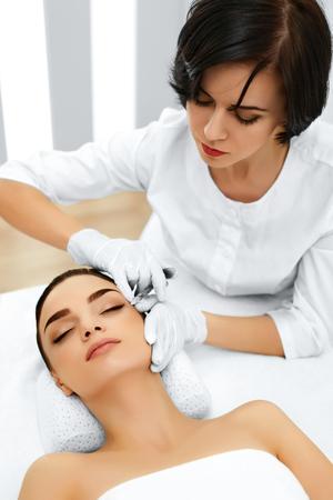 inyeccion: Cirugía plástica. Hermosa mujer joven consigue cosmético relleno dérmico Inyección En Cara En Salón de Belleza. Reducción de las arrugas Tratamiento. Cosmetología. Cara de belleza. Contorno Procedimiento. Mesoterapia Foto de archivo