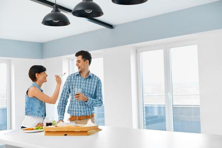 pareja comiendo: Comiendo comida. Sonrisa de la mujer joven que introduce a su Hombre cari�oso de Interior. Pareja comiendo pizza, soda beber y divertirse juntos en casa. Comida r�pida, relaciones, ocio y estilo de vida Concepto.