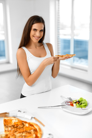 unhealthy diet: Eating Italian Food. Closeup Portrait Of Happy Healthy Caucasian Woman Eating Pizza Indoors. Unhealthy Fast Food Nutrition. Dieting, Diet And Lifestyle Concept. Stock Photo