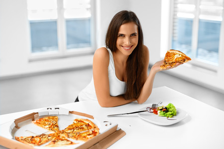 comida italiana: Eating Italian Food. Closeup Portrait Of Happy Healthy Caucasian Woman Eating Pizza Indoors. Unhealthy Fast Food Nutrition. Dieting, Diet And Lifestyle Concept. Foto de archivo