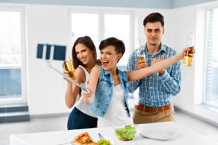 mamadera: Party Home. Happy Friends Taking Selfie Photo With Smartphone Selfie Stick. People Eating Pizza, Drinking Beer And Celebrating Holiday Indoors. Friendship, Leisure, Technology Concept. Celebration.