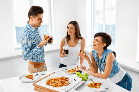 food concept: Eating Food. Group Of Happy Friends Having Dinner Party At Home. Cheerful People Laughing, Eating Pizza And Drinking Soda While Having Fun Together. Fast Food, Friendship, Leisure Concept.