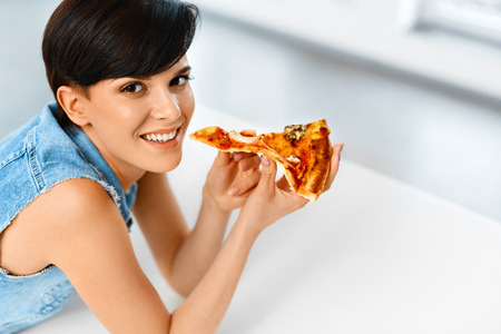 comida italiana: Eating Pizza. Portrait Of Attractive Caucasian Smiling Healthy Woman Eating Italian Food In Modern Kitchen At Home. Fast Food Nutrition. Diet And Lifestyle Concept. Foto de archivo