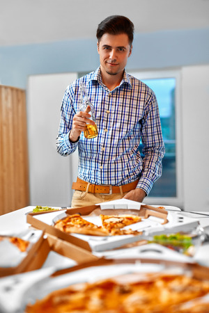 mamadera: Dinner. Happy Young Man Eating Tasty Pizza And Drinking Beer At The Home Party. Fast Food, Nutrition, Leisure Concept. Lifestyle