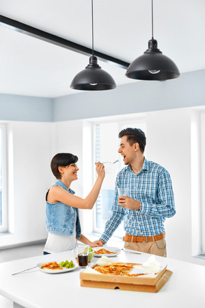 couple amoureux: Eating Food. Smiling Young Woman Feeding Her Loving Man Indoors. Couple Eating Pizza, Drinking Soda And Having Fun Together At Home. Fast Food, Relationships, Leisure And Lifestyle Concept. Banque d'images