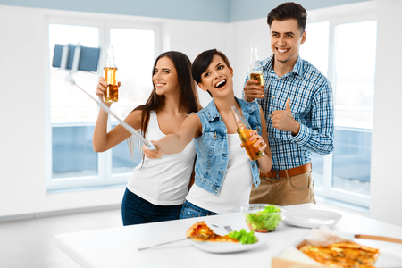 people eating: Party Home. Happy Friends Taking Selfie Photo With Smartphone Selfie Stick. People Eating Pizza, Drinking Beer And Celebrating Holiday Indoors. Friendship, Leisure, Technology Concept. Celebration.