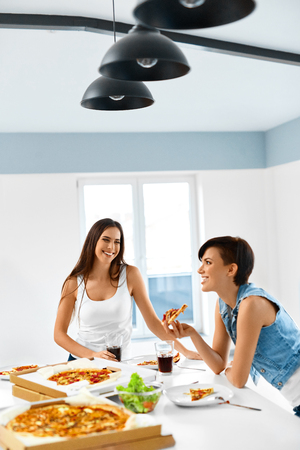 fast meal: Eating Fast Food. Happy Beautiful Girl Friends Laughing, Eating Pizza And Drinking Cold Soda At Home Party. Women Having Dinner Together, Enjoying Meal. Leisure, Friendship, Celebration Concept.
