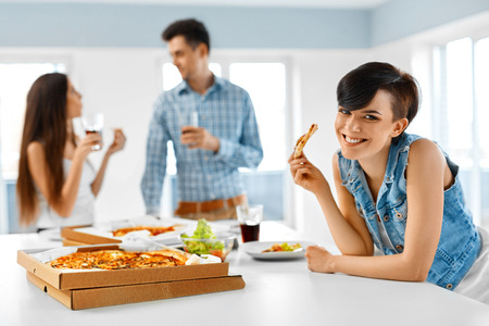 eating fast food: Home Party. Close Up Of Happy Friends Having Dinner Indoors. People Laughing, Eating Pizza And Drinking Soda While Having Fun Together. Fast Food, Friendship, Leisure Concept. Celebration.
