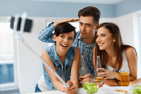 friends drinking: Party. Group Of Happy Friends Making Self Portrait Photo Using Smartphone Selfie Stick, Celebrating Holiday. People Having Fun, Collecting Bright Moments. Friendship, Leisure, Celebration Concept