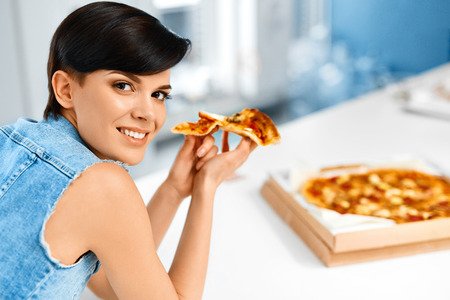 comida italiana: Eating Italian Food. Closeup Portrait Of Happy Healthy Caucasian Woman Eating Pizza Indoors. Fast Food Nutrition. Lifestyle Concept.