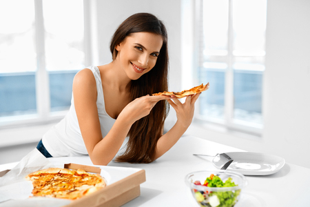comida italiana: Eating Pizza. Portrait Of Attractive Caucasian Smiling Healthy Woman Eating Italian Food In Modern Kitchen At Home. Fast Food Nutrition. Dieting, Diet And Lifestyle Concept.