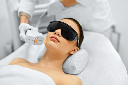 Hautpflege. Junge Frau empfangen Gesichtsbehandlung, Entfernen Pigmentierung Bei Cosmetic Clinic. Intense Pulsed Light Therapy. IPL. Verjüngung, Foto Facial Therapy. Anti-Aging-Verfahren.