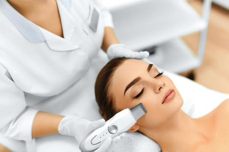 procedures: Skin Care. Close-up Of Beautiful Woman Receiving Ultrasound Cavitation Facial Peeling. Ultrasonic Skin Cleansing Procedure. Beauty Treatment. Cosmetology. Beauty Spa Salon. Stock Photo