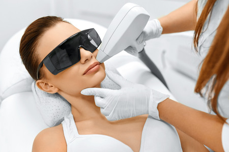 removal: Face Care. Facial Laser Hair Removal. Beautician Giving Laser Epilation Treatment To Young Womans Face At Beauty Clinic. Body Care. Hairless Smooth And Soft Skin. Health And Beauty Concept. Stock Photo