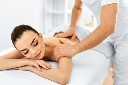massages: Spa Femme. Traitement de beauté. Belle jeune fille de race blanche saine détente avec la main Procédure massage dans le salon Spa. Masseur Masser son dos. Soin du corps. Soins de la peau, de bien-être, Bien-être. Banque d'images