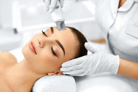 aesthetic: Skin Care. Close-up Of Beautiful Woman Receiving Ultrasound Cavitation Facial Peeling. Ultrasonic Skin Cleansing Procedure. Beauty Treatment. Cosmetology. Beauty Spa Salon. Stock Photo