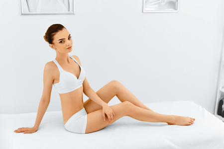 beauty body: Beauty Woman. Portrait Of Beautiful Smiling Spa Model Woman Touching Her Face Lying In Spa Salon. Perfect Fresh Pure Skin. Spa Body And Skin Care, Cleansing And Moisturizing Concept. Healthy Lifestyle Stock Photo