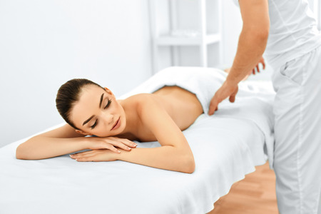 the caucasian beauty: Spa Woman. Beauty Treatment. Beautiful Young Healthy Caucasian Girl Relaxing With Hand Massage Procedure In The Spa Salon. Masseur Massaging Her Back. Body Care. Skin Care, Wellness, Wellbeing.