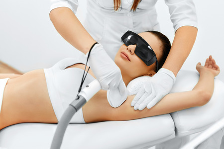 beauty treatment clinic: Body Care. Underarm Laser Hair Removal. Beautician Removing Hair Of Young Womans Armpit. Laser Epilation Treatment In Cosmetic Beauty Clinic. Hairless Smooth And Soft Skin. Health And Beauty Concept. Stock Photo