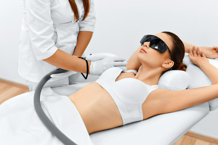 laser treatment: Body Care. Underarm Laser Hair Removal. Beautician Removing Hair Of Young Womans Armpit. Laser Epilation Treatment In Cosmetic Beauty Clinic. Hairless Smooth And Soft Skin. Health And Beauty Concept. Stock Photo