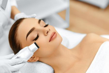 スキンケア。超音波キャビテーション顔ピーリングを受ける美人のクローズ アップ。超音波皮膚洗浄手順。美容トリートメント。美容。サロン。 写真素材
