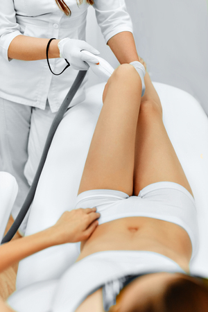 beauty treatment clinic: Body Care. Legs Laser Hair Removal. Beautician Removing Hair Of Young Womans Leg. Laser Epilation Treatment In Cosmetic Beauty Clinic. Hairless Smooth And Soft Skin. Health And Beauty Concept. Stock Photo