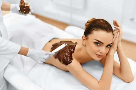receiving: Body Care. Spa Treatment. Portrait Of Beautiful Smiling Young Woman Receiving Cosmetic Chocolate Body Mask At Beauty Salon. Skin Care. Healthy Lifestyle