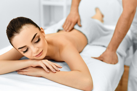 the caucasian beauty: Body Care. Spa Woman. Beauty Treatment Concept. Masseur Doing Hand Massage On Relaxed Beautiful Young Caucasian Womans Body In The Spa Salon. Skin Care, Wellness, Wellbeing. Stock Photo