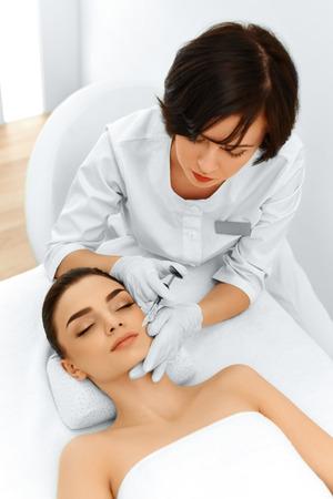 Plastische chirurgie. Mooie jonge vrouw krijgt cosmetische dermal filler Injectie In Gezicht In Beauty Salon. Vermindering van rimpels Behandeling. Cosmetologie. Schoonheid Gezicht. Contouren Procedure. Mesotherapie Stockfoto