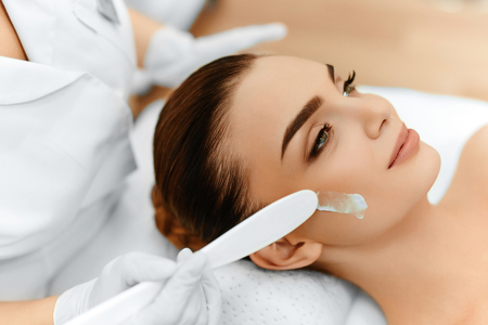 スキンケア。若い女性の顔の美容保湿クリームを適用するメークアップ アーティストのクローズ アップ。美容顔。美容室でトリートメント。顔の美